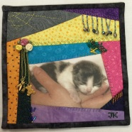 Janis Katz - crazy quilt square with hands and cat